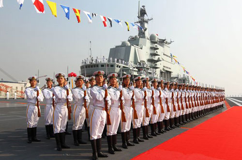 Naval honor guards stand as they wait for a review on China's aircraft carrier, Liaoning, on September 25' 2012