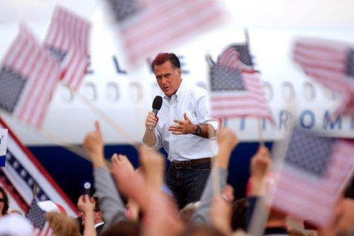 Mitt Romney speaks among waving flags in Pueblo, Colo on Sept. 24, 2012