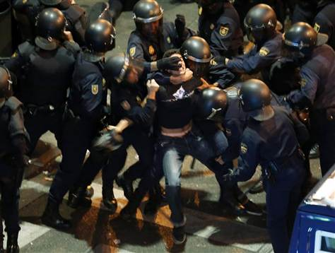 A demonstrator struggles with Spanish National Police riot officers outside the the Spanish parliament in Madrid September 25, 2012
