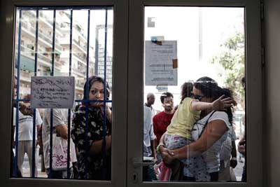 In this New York Times photo, People wait outside Medicins du Monde, a free clinic, in Athens, Greece, September 3, 2012.
