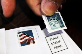 In this Dec. 5, 2011 AP photo, a customer places first class stamps on envelopes at a U.S. Post Office in San Jose, Calif. It'll cost another penny to mail a letter in 2013.