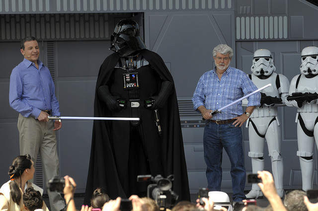 Disney CEO Robert Iger, left, an actor portraying the movie character Darth Vader, center, and Star Wars creator George Lucas, third from right, stand onstage at the Disney Hollywood Studios theme park during the re-opening celebration of the Star Tours motion simulation ride in Lake Buena Vista, Fla., Friday, May 20, 2011. Credit: Phelan M. Ebenhack/AP