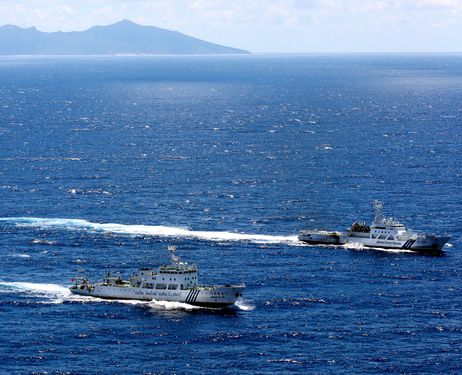 A Chinese marine surveillance ship, foreground, runs side by side with a Japan Coast Guard vessel in waters off Kubashima island, one of the five Senkaku islands, on September 14, 2012. Uotsurishima island is in the background.