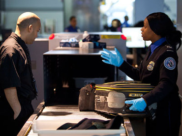 In this Reuters file photo, a Transportation Security Administration (TSA) security agent takes luggage for a second security check at John F. Kennedy Airport in New York.