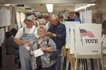 Residents wait in line to pick up ballots at the courthouse in Waterloo, Iowa, when early voting in the state started on September 27, 2012